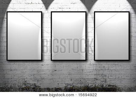 Three empty frames against a white brick wall