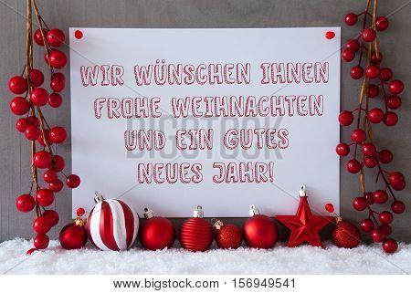 Label With German Text Wir Wuenschen Frohe Weihnachten Und Ein Gutes Neues Jahr Means Merry Christmas And Happy New Year. Red Decoration Like Balls On Snow. Cement Wall As Background