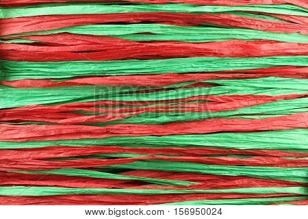 Background - red and green paper raffia strips situated in parallel lines
