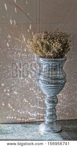 Silver disco mirror vase in hotel lobby.