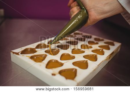 Worker filling mould with piping bag in kitchen