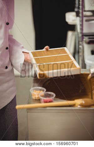 Mid section of worker holding chocolate mould in factory