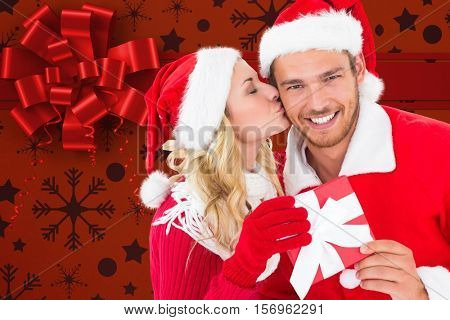 Woman kissing man on cheeks against digitally generated background during christmas time