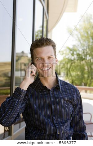 Happy business man on a call outside his office building