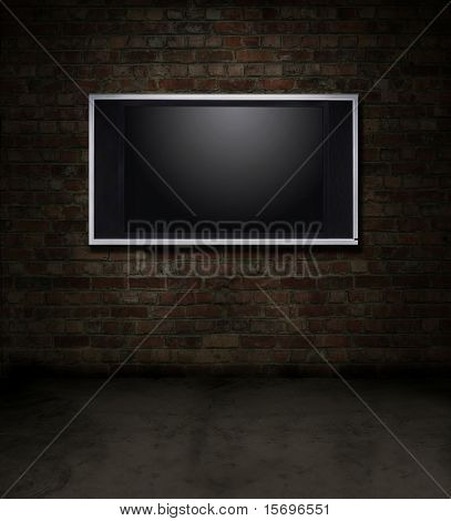 Dark grungy red brick room with a flat screen TV