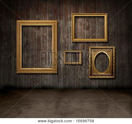 Empty gold frames hanging in a dark wooden room
