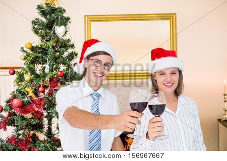 Portrait of happy couple in santa hat toasting red wine during christmas time