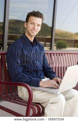 Attractive business man on his laptop outside an office building