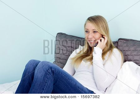 teen girl laying on her bed talking on the phone