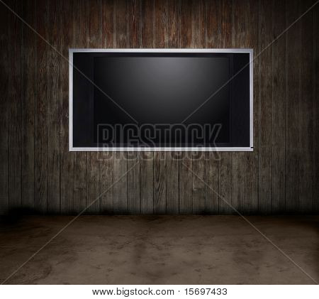 Dark grungy room with a wooden wall and a flat panel TV