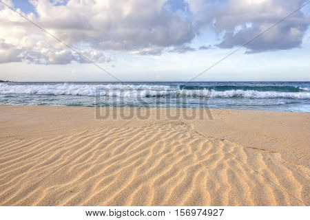 Wide angle closeup of ripples in coarse orange sand as waves roll into shore on Playa Brava on Isla Culebra in Caribbean Sea under diffused natural light