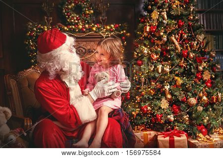 child girl in a nightgown sitting on the lap of Santa Claus around Christmas tree