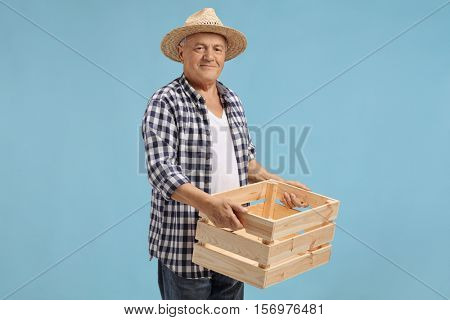 Elderly farmer holding a wooden empty crate isolated on blue background