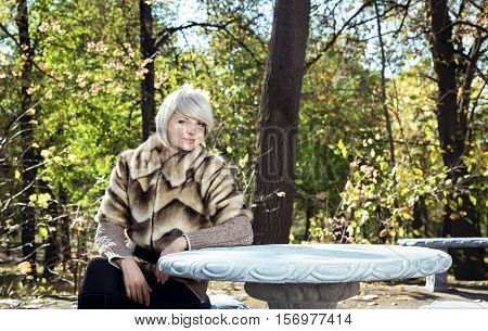 Girl sits at a table in the park. Girl strolls in the autumn park.