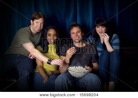 Friends watching a game eating popcorn