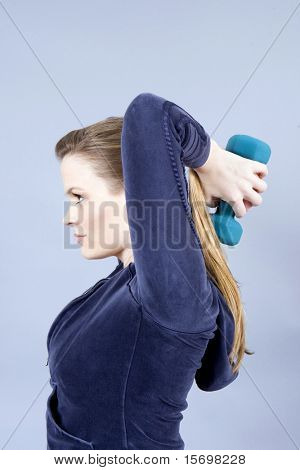 Pretty young woman exercising with free weights