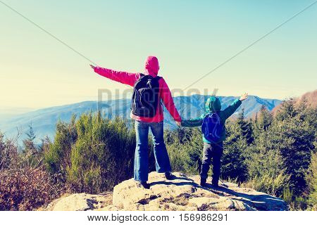 family travel concept- mother and son hiking in scenic mountains