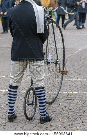 An unidentified men in a vintage clothes ready to ride a penny-farthing bicycle