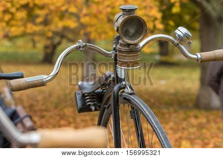 A penny-farthing bicycle with an old headlamp in a park with fallen autumn leaves (soft vintage filter applied)