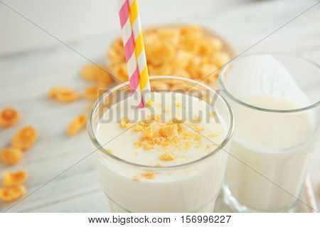 Delicious milkshake with flakes in glass on table, closeup