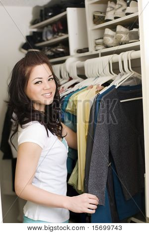 Woman looking at clothes in a closet