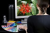 Designer at work. Color samples on table. Vivid picture on computer monitor.