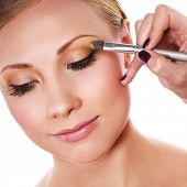 picture of makeup artist  - Makeup artist applying yellow eyeshadow - JPG