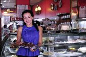 stock photo of confectioners  - owner of a small business store showing her tasty cakes - JPG