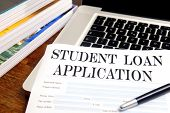image of borrower  - blank student loan application on desktop with books and laptop - JPG