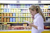 stock photo of grocery-shopping  - woman reading her shopping list in the supermarket with copy space - JPG