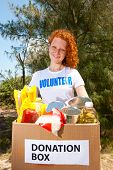 picture of charity relief work  - happy volunteer carrying food donation box - JPG