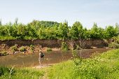 picture of bagpack  - Man with his dog in the river in Holland - JPG