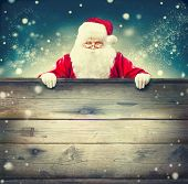 Happy Santa Claus holding blank advertisement wooden banner background with copy space. Smiling Sant poster