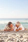 Постер, плакат: Пожилые пары лежа на пляже