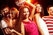 stock photo of night-club  - Group of teens dancing in night club with glamorous girl in front - JPG