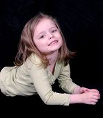 Cute Little Girl Laying On A Black Background poster