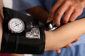 pic of medical assistant  - Medical worker checking blood pressure - JPG