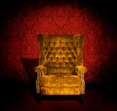 stock photo of grommets  - A grungy gold velvet chair in a dark room with red Victorian wallpaper - JPG