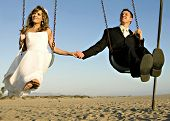 foto of swingset  - Young bride and groom playing on a swing set - JPG