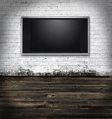 Flat screen television in a dark room with white bricks
