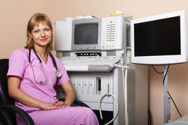 picture of medical equipment  - Portrait of female doctor near modern ultrasound equipment at modern clinic - JPG