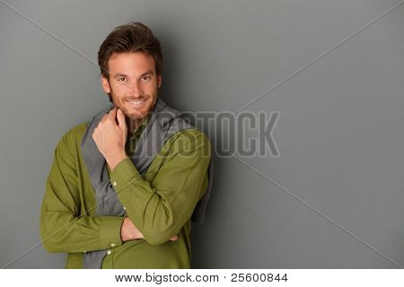 Laughing man posing at wall in smart shirt, grey background, copyspace.?