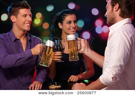 Happy companionship having fun in nightclub, clinking glasses, smiling.?