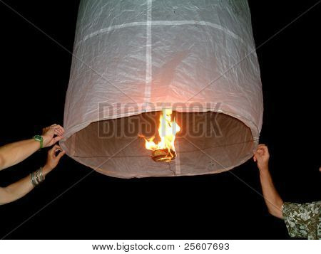 two people holding a flying fire lantern, khao lak, thailand