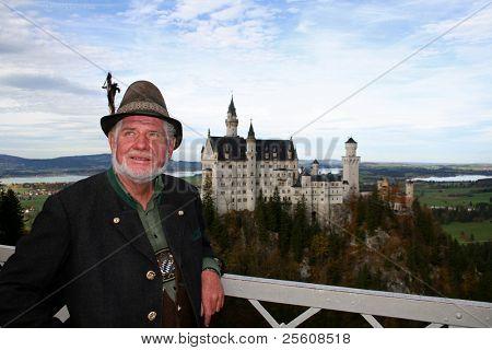 bavarian man in lederhosen posing infront of neuschwanstein castle