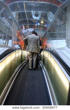 businessman travelling on airport escalator