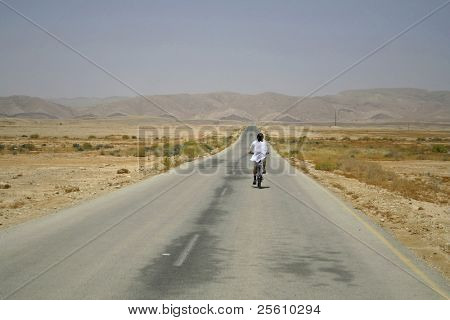 man cycling on sede boker desert road, israel