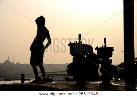 little kid playing on harbour at sunset, bosphorus, istanbul, turkey