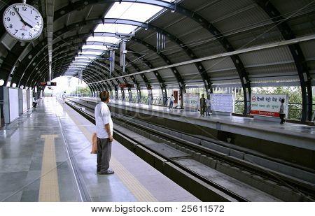 man awaiting metro at station, delhi, india