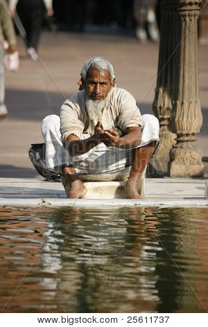 Old man performing ablution at Jama Masjid, Delhi, India